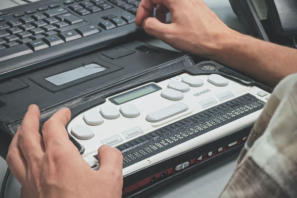 hands on a SENSE brail computer input machine with a keyboard in front of that